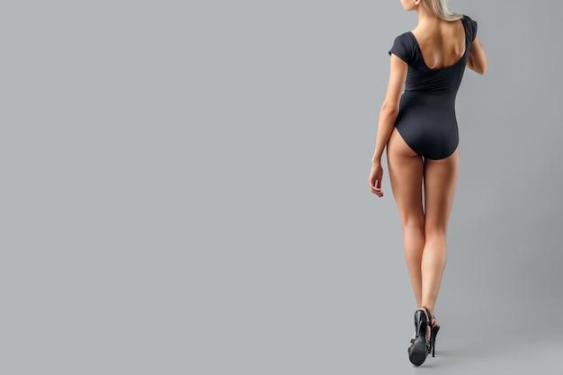 Bella donna con le gambe lunghe su sfondo grigio. gambe sexy in scarpe nere tacco alto. Foto Premium
