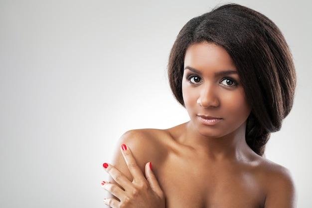 Bella donna con le spalle nude sta toccando la spalla Foto Gratuite