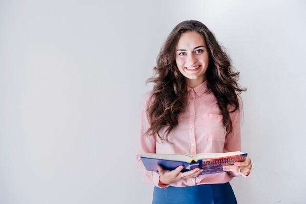 Bella donna con libro in studio Foto Gratuite