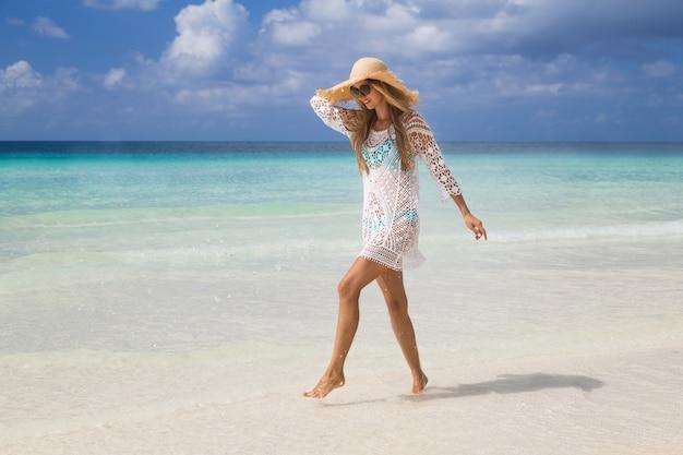 Bella donna con lunghi capelli biondi in bikini blu rilassante sulla spiaggia tropicale con sabbia bianca Foto Premium