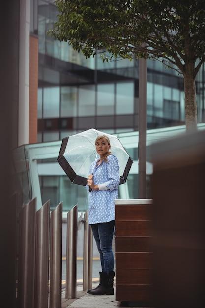 Bella donna con ombrello e in piedi sulla strada Foto Gratuite