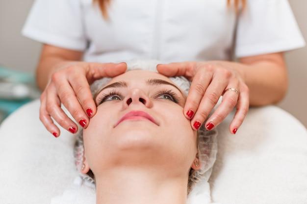 Bella donna con un trattamento di bellezza viso massaggio Foto Premium