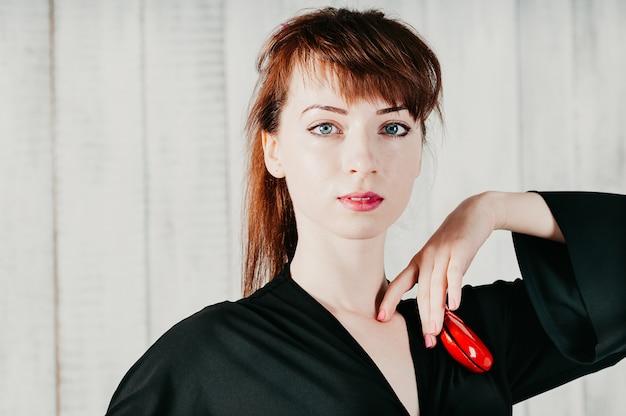 Bella donna dagli occhi azzurri in abito nero, con nacchere rosse, sfondo chiaro Foto Premium