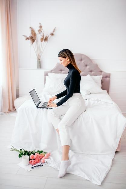 Bella donna di aspetto europeo lavora al computer in una stanza luminosa a casa, lavoro online Foto Premium