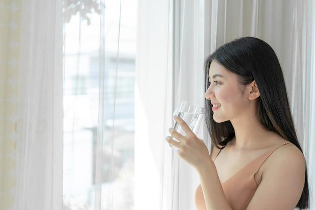 Bella donna di bellezza asiatica ragazza carina sentire felice bere acqua potabile per una buona salute al mattino Foto Gratuite