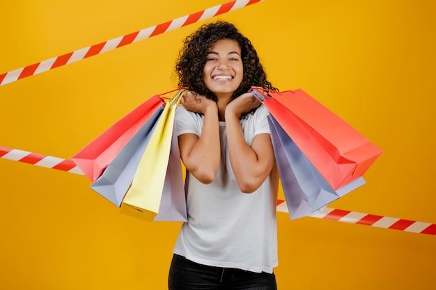 Bella donna di colore africana con i sacchetti della spesa variopinti isolati sopra giallo con nastro adesivo Foto Premium