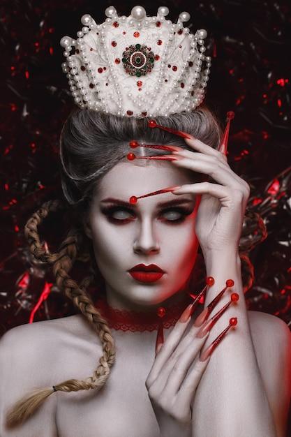 Bella donna faccia con trucco creativo fashion art e con lunghe unghie rosse Foto Premium