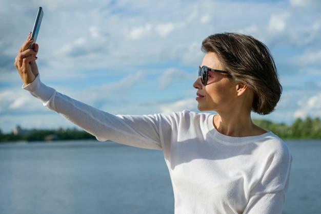Bella donna facendo selfie usando smartphone. Foto Premium