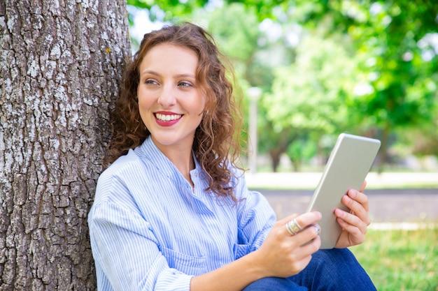 Bella donna felice che usando internet mobile sul tablet Foto Gratuite