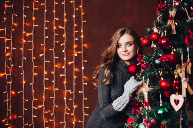 Bella donna in abito grigio in piedi contro l'albero di natale decorato. Foto Premium