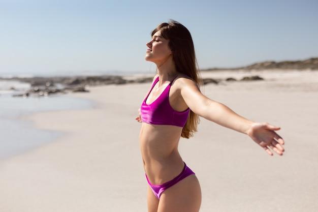 Bella donna in bikini con le braccia distese in piedi sulla spiaggia sotto il sole Foto Gratuite