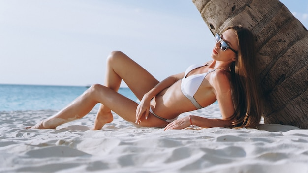 Bella donna in costume da bagno dall'oceano che giace sotto il palmo Foto Gratuite
