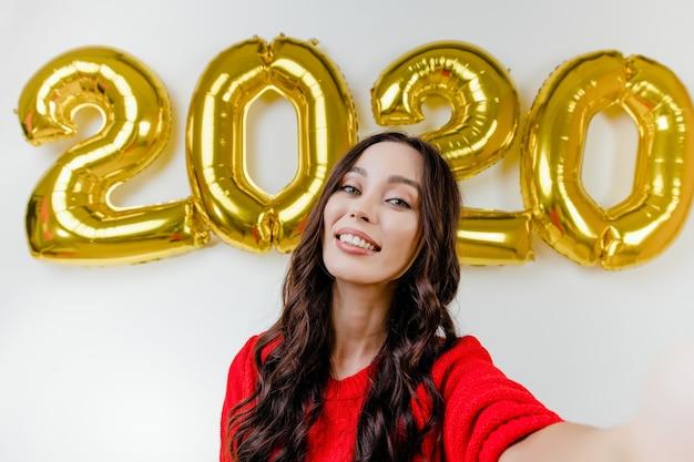 Bella donna in maglione rosso che fa selfie divertente davanti ai palloni del nuovo anno 2020 Foto Premium