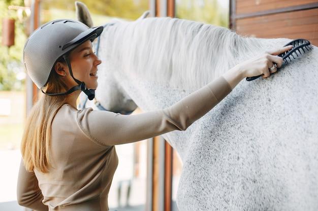 Bella donna in piedi con un cavallo Foto Gratuite