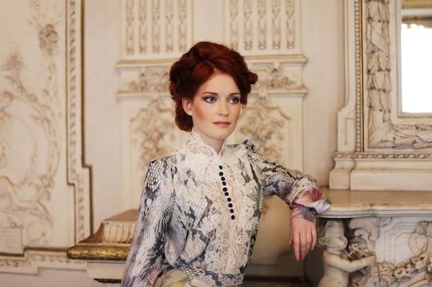 Bella donna in piedi nella stanza del palazzo. Foto Premium