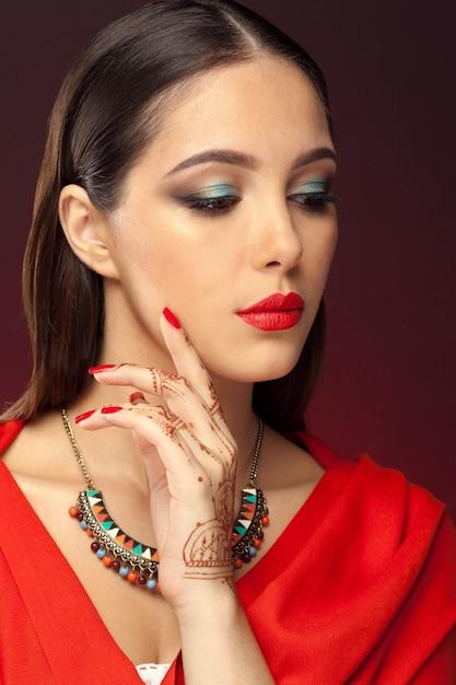 Bella donna in stile orientale con mehendi su oscurità Foto Premium