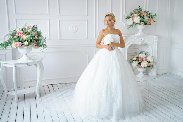 Bella donna in un abito da sposa con un bel trucco e capelli Foto Premium