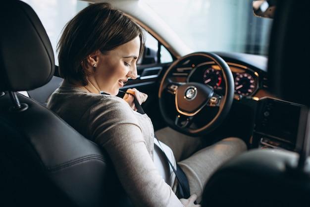 Bella donna incinta che guida in auto Foto Gratuite