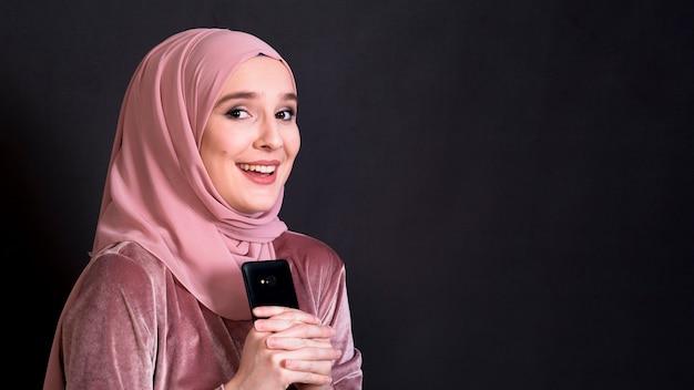 Bella donna musulmana che esamina il telefono cellulare della tenuta della macchina fotografica su fondo nero Foto Gratuite