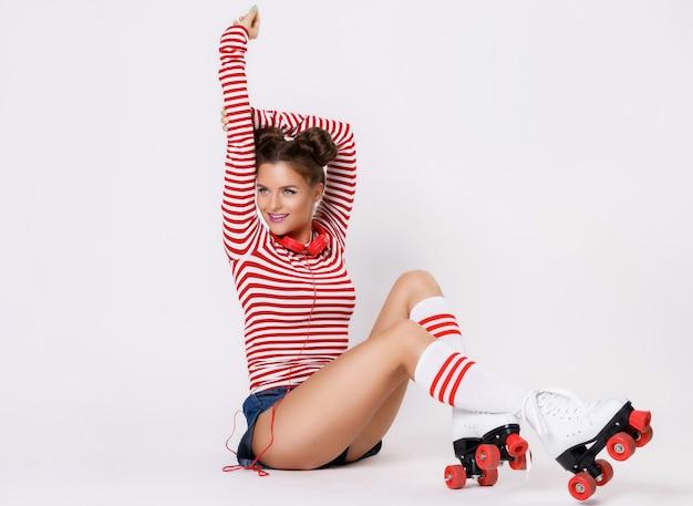 Bella donna nei pattini di rullo e con le cuffie rosse Foto Premium