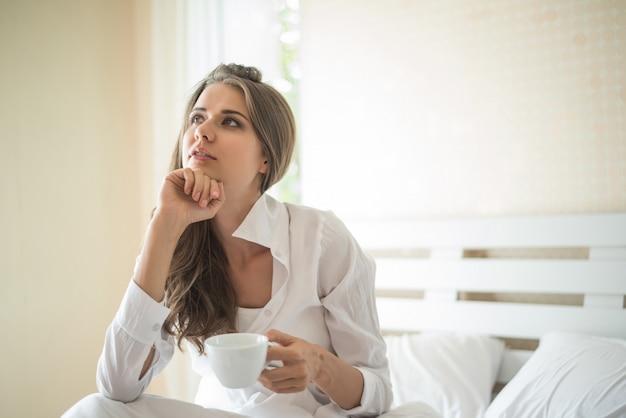 Bella donna nella sua camera da letto bere caffè al mattino Foto Gratuite