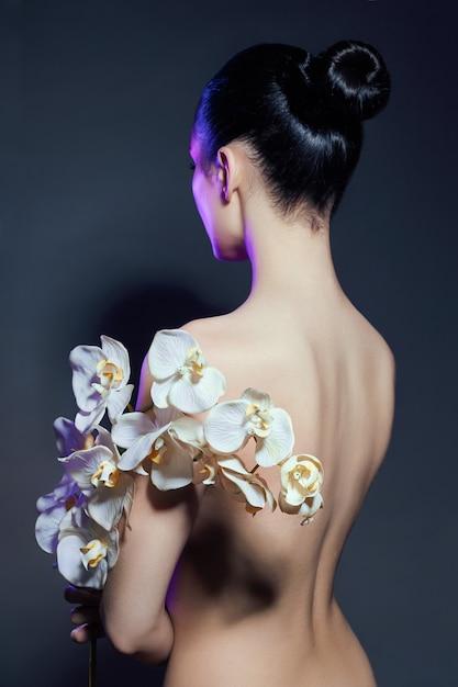 Bella donna nuda con un ramo di orchidea bianca Foto Premium