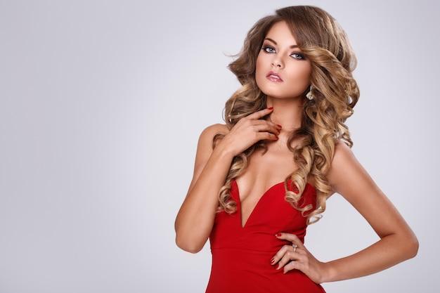 Bella donna riccia in abito rosso Foto Gratuite