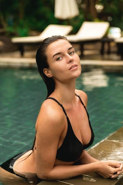 Bella donna rilassante in piscina Foto Premium