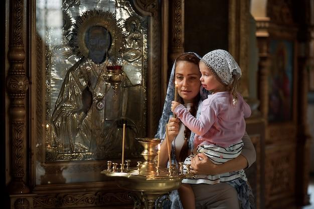 Bella donna russa in una sciarpa e con i capelli rossi in possesso di una bambina e accende una candela di fronte a un'icona nella chiesa ortodossa russa. Foto Premium