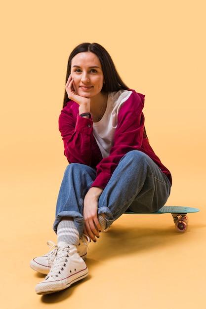 Bella donna seduta su skateboard Foto Gratuite
