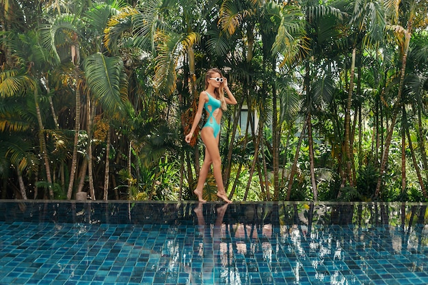 Bella donna sexy in bikini blu che sta piscina vicina. Foto Premium