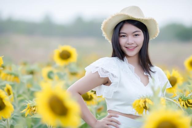 Bella donna sexy in un abito bianco che cammina su un campo di girasoli Foto Gratuite