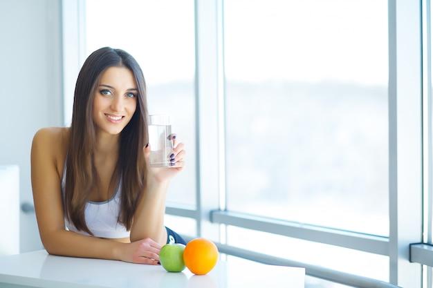 Bella donna sorridente che cattura la pillola della vitamina. integratore alimentare Foto Premium