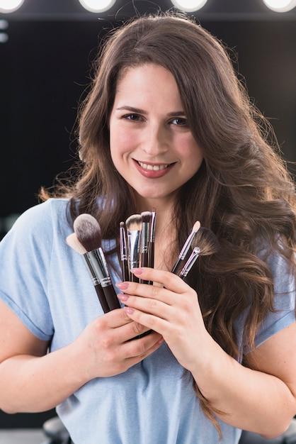 Bella donna sorridente con pennelli trucco Foto Gratuite