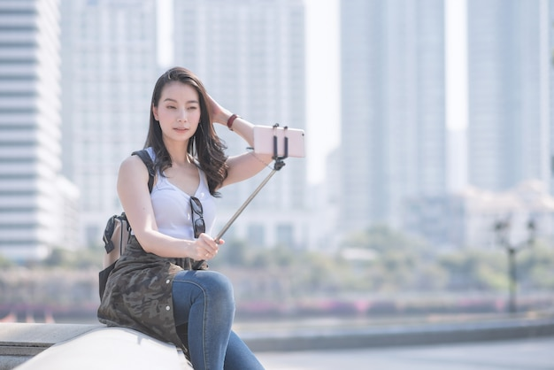 Bella donna turistica asiatica prendendo autoscatti su uno smartphone in città urbana del centro. Foto Premium