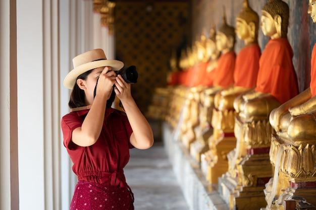 Bella donna turistica videocamera per catturare i ricordi. tempio di wat arun Foto Premium
