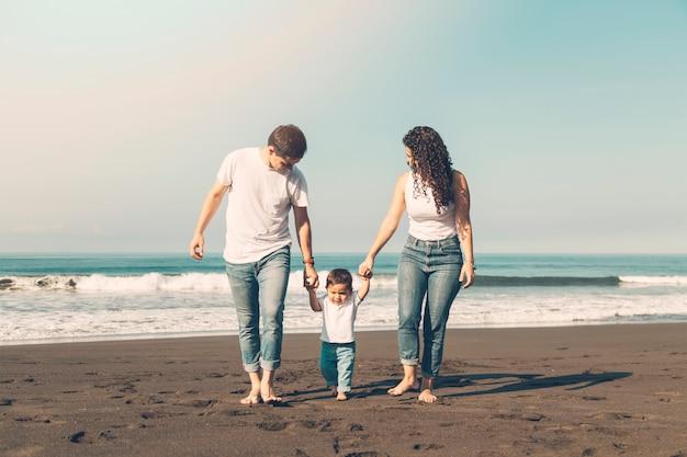 Bella famiglia camminando lungo la spiaggia Foto Gratuite