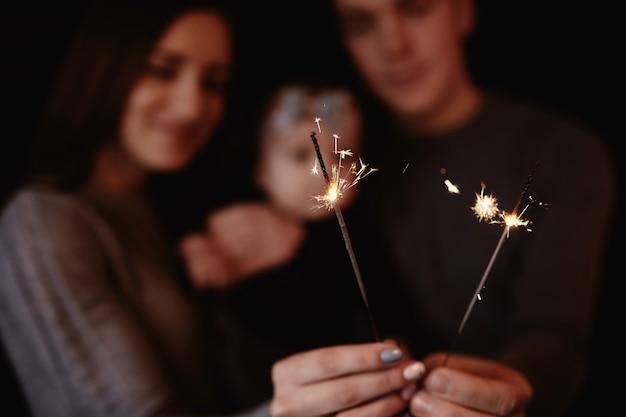 Bella famiglia con bambino festeggia il natale e tiene le stelle filanti Foto Premium