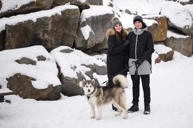 Bella famiglia, un uomo e una ragazza nella foresta invernale con cane. gioca con il cane siberian husky. Foto Premium