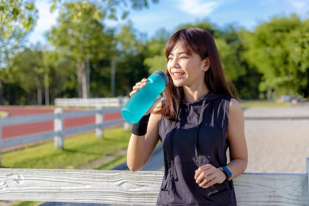 Bella felice giovane donna asiatica bere la sua acqua al mattino in una pista da corsa prima di iniziare il suo esercizio Foto Premium