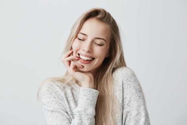 Bella femmina che chiude gli occhi per la gioia, con lunghi capelli biondi e un sorriso gentile. la donna allegra tiene la mano sotto il mento, ha compiaciuta espressione del viso. espressione del viso ed emozioni positive Foto Gratuite