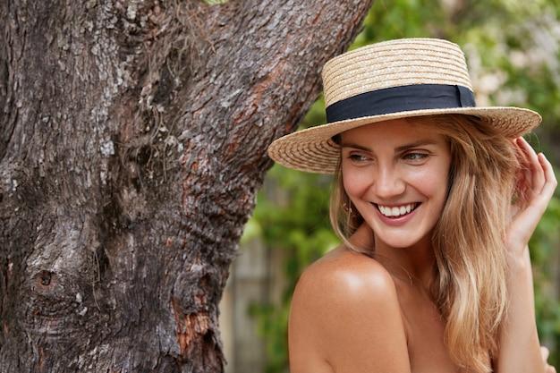 Bella femmina con corpo nudo, distoglie lo sguardo mentre posa vicino al grande albero all'aperto, indossa un cappello estivo alla moda, gode di una buona ricreazione ai tropici, ha un sorriso piacevole e affascinante. persone, concetto di bellezza Foto Gratuite