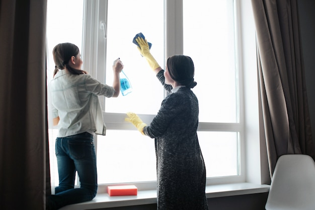 Bella finestra caucasica castana di pulizia della figlia e della madre nella sala. spruzzo di uso della ragazza che lavora duro. finestra di lavaggio della giovane donna. lavorano insieme. Foto Premium