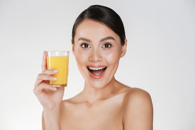 Bella foto di donna seminuda con i capelli scuri in panino e ampio sorriso che beve il succo d'arancia da un vetro trasparente, isolato su un muro bianco Foto Gratuite