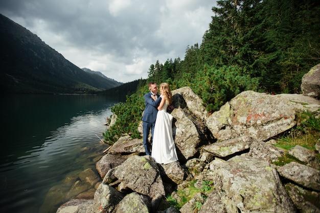 Bella foto di nozze sul lago di montagna. felice coppia asiatica in amore, sposa in abito bianco e lo sposo in tuta Foto Premium