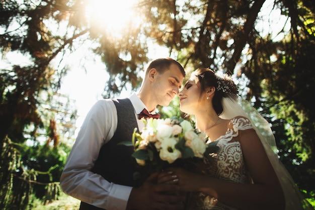 Bella giornata di sole. coppie di cerimonia nuziale che propongono sui precedenti della natura Foto Premium