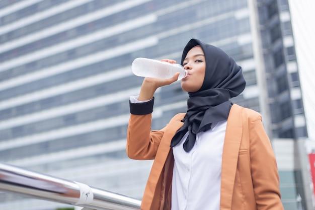 Bella giovane acqua potabile musulmana asiatica. Foto Premium