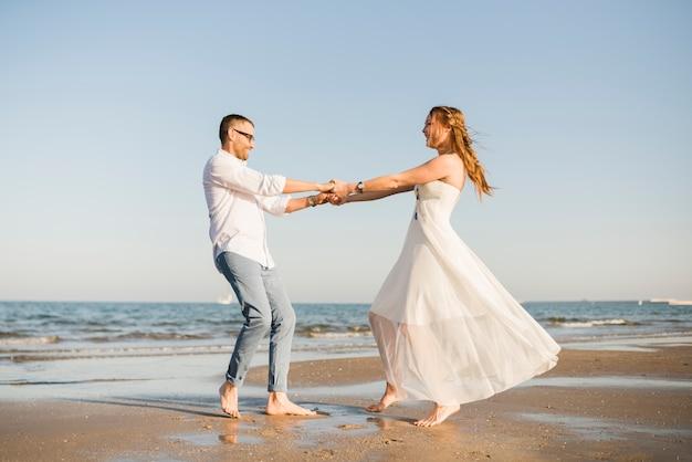 Bella giovane coppia ballando insieme vicino al litorale in spiaggia Foto Gratuite