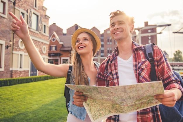 Bella giovane coppia di viaggiatori sta usando una mappa. Foto Premium