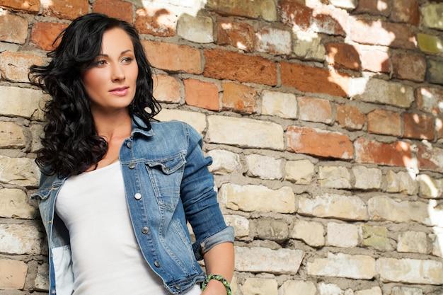 Bella giovane donna al muro di mattoni Foto Gratuite
